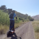 Man with backpack riding an off road electric scooter