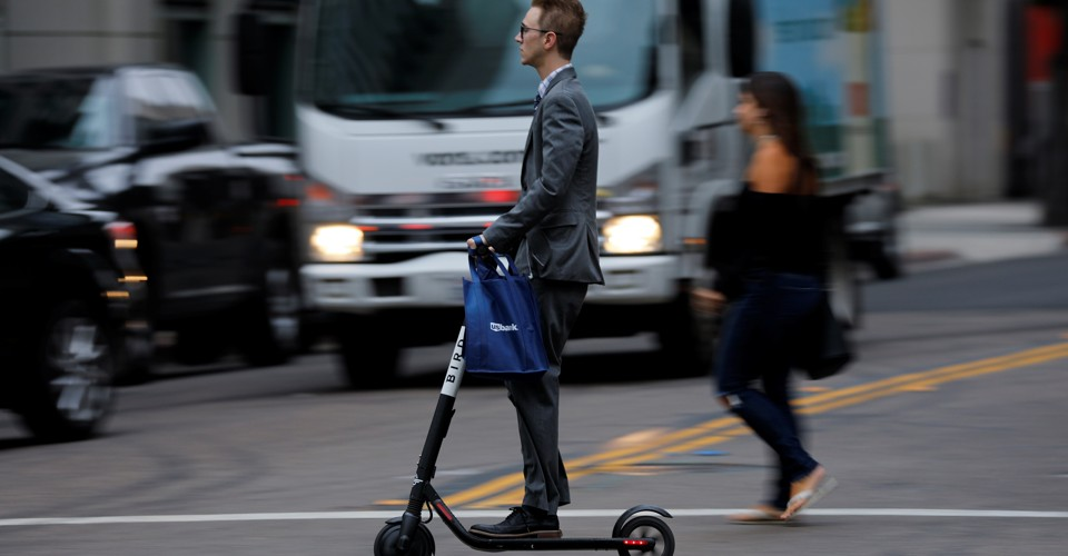 A man in a suite rides an electric scooter