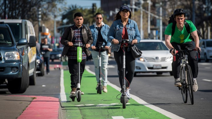 A group of scooter riders being passed by a bike